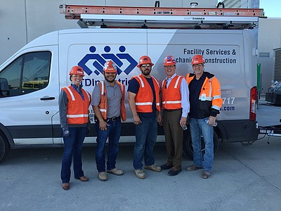 TDIndustries group picture of on-site workers in front of a white TDIndustries utility van