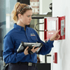 woman checking fire alarm panel