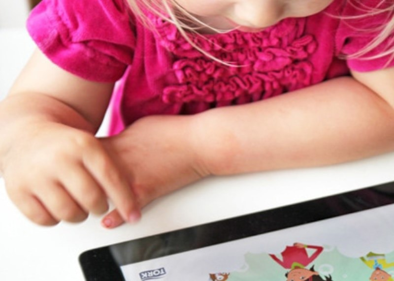 Ella wearing a pink ruffle shirt learns on her iPad while at school