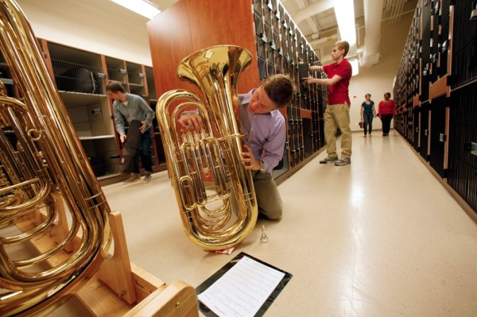 Boy practicing tuba on floor of instrument storage room